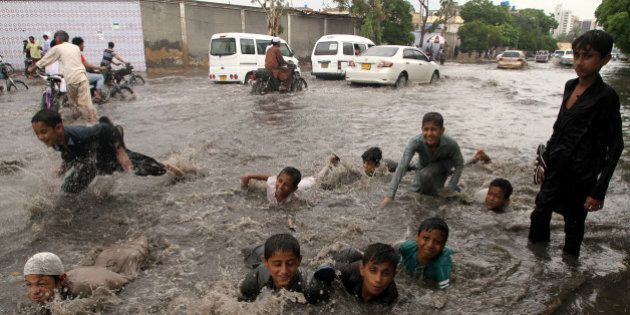 Youngsters play in a flooded road caused by heavy rains in Karachi, Pakistan, Wednesday, June 29, 2016....