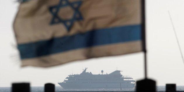 An Israeli flag flutters in the wind as a naval vessel (not seen) escorts the Mavi Marmara, a Gaza-bound...