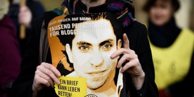 An Amnesty International activist holds a picture of Saudi blogger Raif Badawi during a protest against...