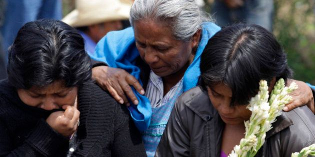 Women cry during the funeral of people who were killed in a bus accident in Coxcatlan June 25, 2012....
