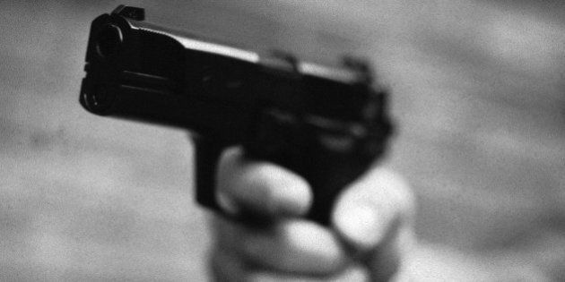 Hand holding gun, close-up,