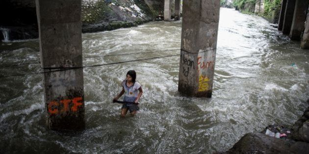A girl plays at a swollen creek under a bridge in Manila on October 16, 2016.Typhoon Sarika lashed the...