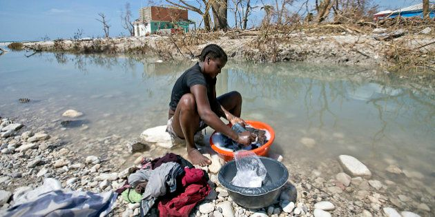 Natalie Joseph cleans clothes in a river cutting through Roche a Bateau, Haiti on Sunday, Oct. 9, 2016....