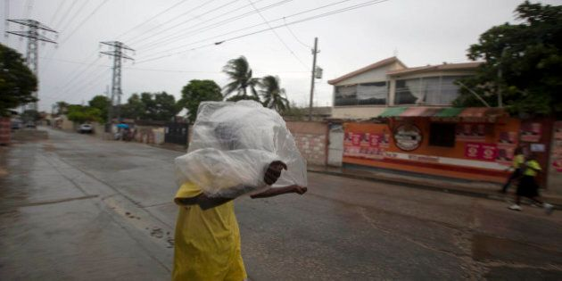 A man crosses a street using a garbage bag as protection from a light rain, in Port-au-Prince, Haiti,...