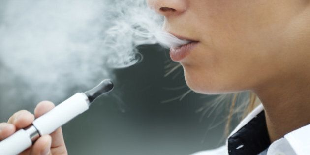 closeup of woman smoking e-cigarette and enjoying smoke. Copy