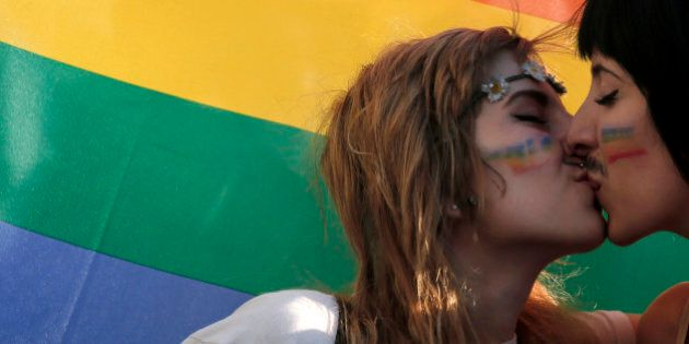 FILE - In this Saturday, June 14, 2014 file photo, two women kiss in front of a rainbow flag, the symbol...