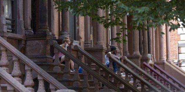 Brownstone residents sit on steps in central Harlem, New York, U.S., on Sunday, Aug. 10, 2014. Developers...