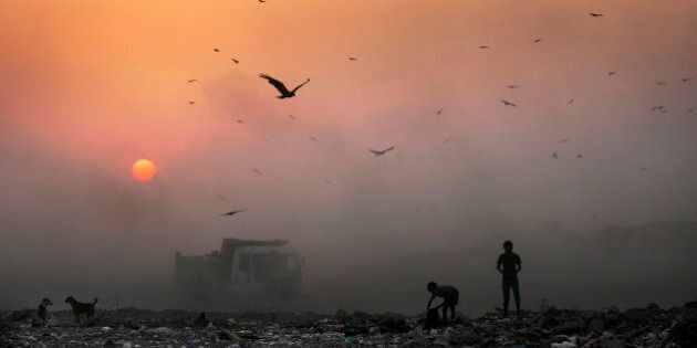 FILE- In this Oct. 17, 2014, file photo, a thick blanket of smoke is seen against the setting sun as young ragpickers search for reusable material at a garbage dump in New Delhi, India. India launched the Air Quality Index Friday to measure air quality across the nation that is home to some of the most polluted cities in the world. A groundbreaking agreement struck Wednesday, Nov. 12, 2014, by the United States and China puts the world's two worst polluters on a faster track to curbing the heat-trapping gases blamed for global warming. (AP Photo/Altaf Qadri, File)