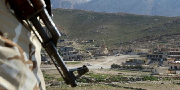FILE - In this Sunday Jan. 11, 2015 file photo, a Yazidi fighter protects the Sharaf al-Deen temple shrine,...