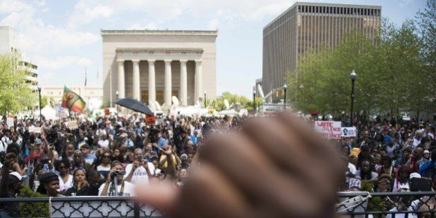 A demonstrator raises his fist in the air as others protest in front of City Hall in Baltimore, Maryland,...