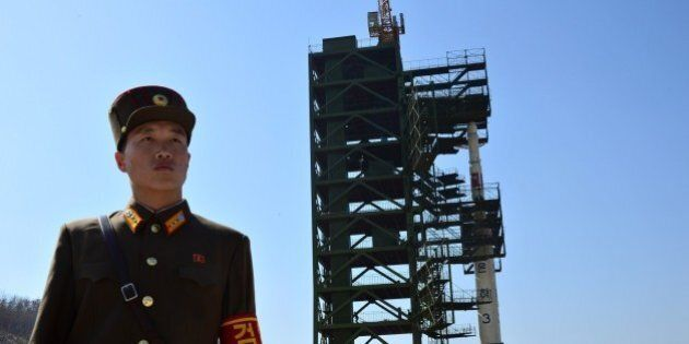 A North Korean soldier stands guard in front of the Unha-3 rocket at the Sohae Satellite Launch Station...