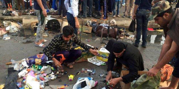 Street vendors collect their belongings after deadly bombing attacks in Sadr City, Baghdad, Iraq, Sunday,...