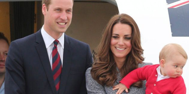 Britain's Prince William, left,  and Kate, the Duchess of Cambridge, center, along with son Prince George, stand atop of the stairs to say good bye as they board their flight in Canberra,  Australia, Friday, April 25, 2014. The Duke and Duchess concluded their three week state visit by attending the Anzac Day dawn service and parade, laying a wreath and planting a Lone Pine tree before departing for London with son Prince George.(AP Photo/Rob Griffith)