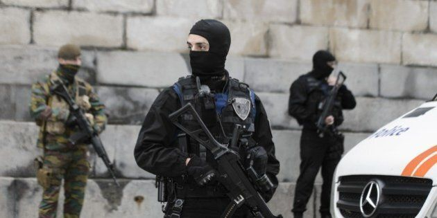 Belgian police officers and soldiers stand guard outside the Brussels Palace of Justice during the appearance...