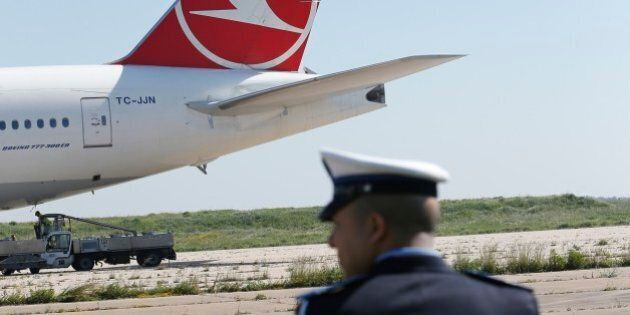 Police officer stands next to a Turkish aircraft on a runway away from the airport building of Casablanca,...