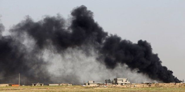 Smoke billows from what is believed to be an oil field which was set alight by Islamic State (IS) group...