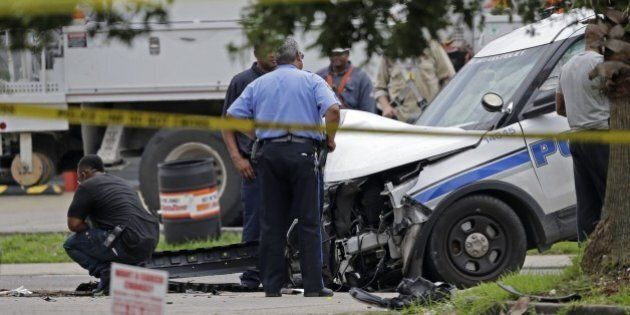 Investigators look over a New Orleans Police department vehicle in which one officer was shot and killed...