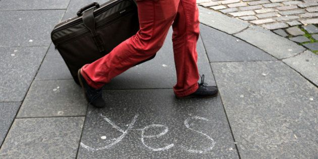 A person walks by a message left by a member of the Yes campaign written on a pavement, in Edinburgh,...