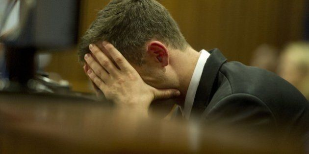 South African Paralympic track star Oscar Pistorius react during his trial in Court in Pretoria on April...