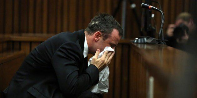 South African Paralympic track star Oscar Pistorius wipes his face during his trial in Court in Pretoria...