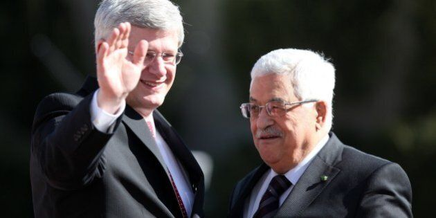 Canadian Prime Minister Stephen Harper (L) waves as he is welcomed by Palestinian President Mahmoud Abbas...