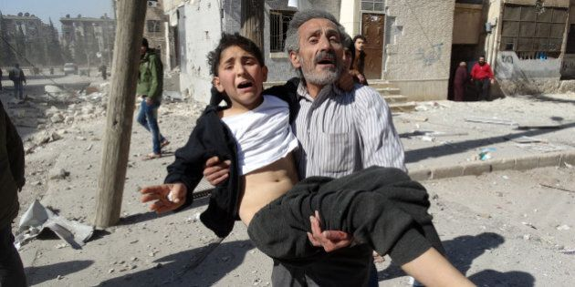 A Syrian man carries a wounded child following a reported air strike attack by government forces on the...