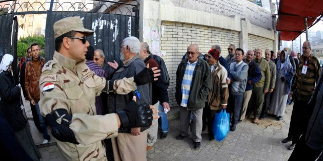 Egyptian security forces stand guard outside a polling station as people queue to vote on a new constitution...
