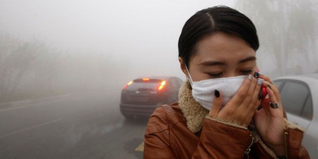 A woman wearing a mask covers her mouth with her hands as she walks in the smog in Harbin, northeast...