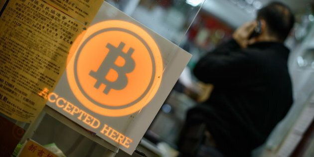 A man talks on a mobile phone in a shop displaying a bitcoin sign during the opening ceremony of the...