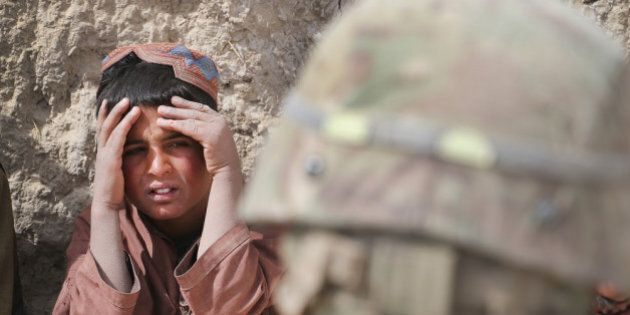 KANDAHAR, AFGHANISTAN - MARCH 02: A young boy listens as soldiers with the Afghan National Army (ANA)...