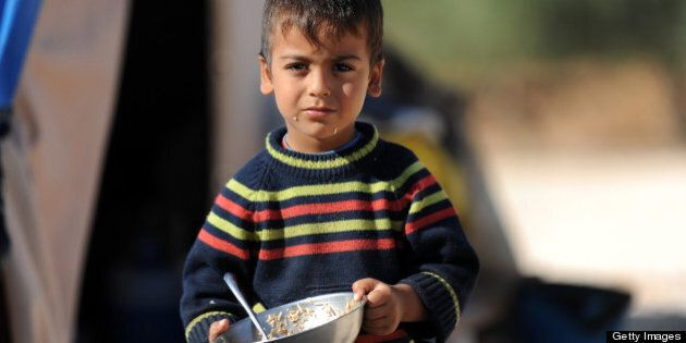 A Syrian boy looks on as he holds his plate of food in a newly built refugee camp at the village of Qah,...