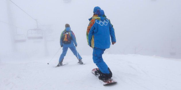 A volunteer skis through the fog prior to the postponed men's snowboard cross competition at the Rosa...