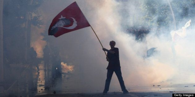 Tear gas surrounds a protestor holding a Turkish flag with a portrait of the founder of modern Turkey...