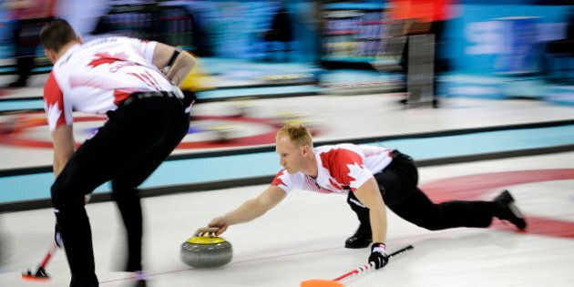 Canada's skip Brad Jacobs, right, delivers the rock while his teammate Ryan Harnden, Left, prepares to...