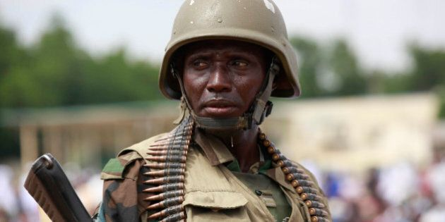 FILE -In this file photo taken Thursday, Aug. 8, 2013, a Nigerian soldier stand guards during Eid al-Fitr...