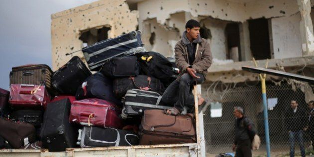 Palestinians await permission to enter Egypt as they gather inside the Rafah border crossing between...