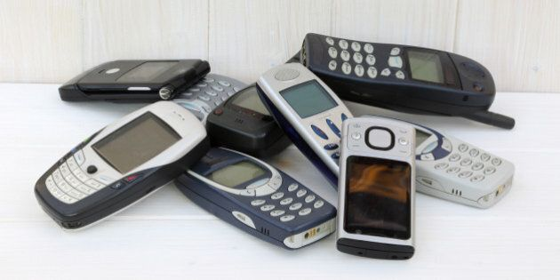 Nine outdated mobile phones stored in pile on