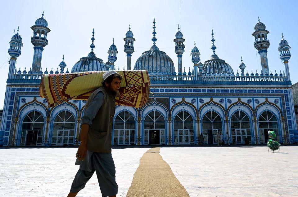 Pakistan - Un homme transporte sur son épaule un tapis de prière devant une mosquée...