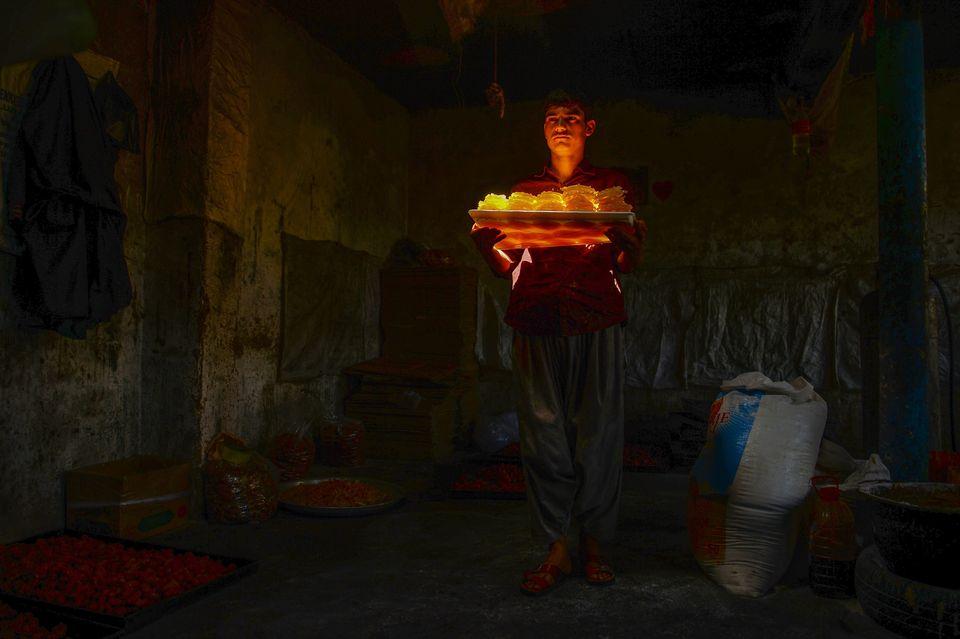 Afghanistan - Un travailleur transporte des sucreries dans un atelier traditionnel à Herat, au...