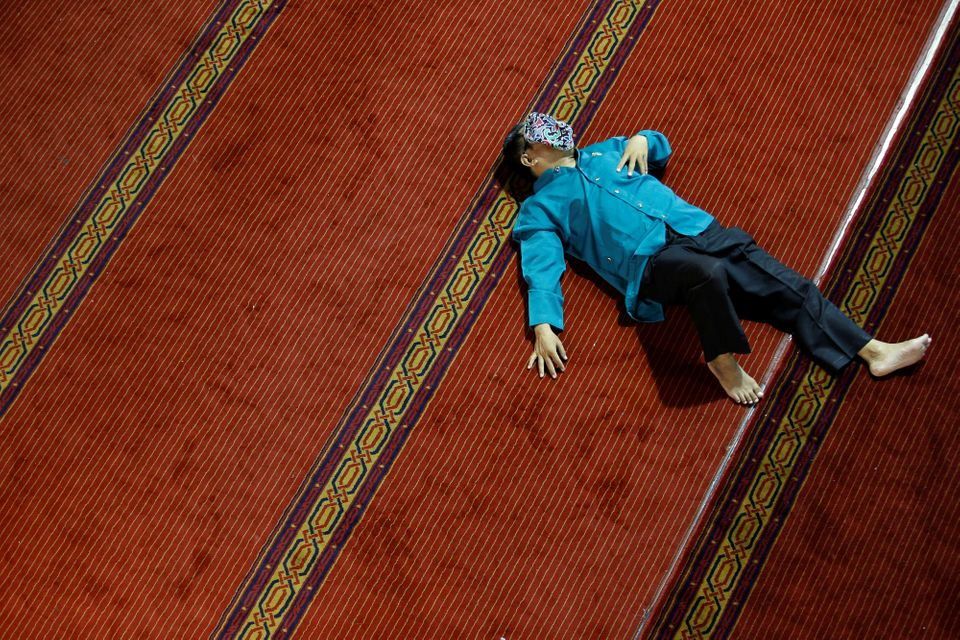 Indonésie - Un homme se repose en attendant le Iftar à la mosquée Istiqlal à...