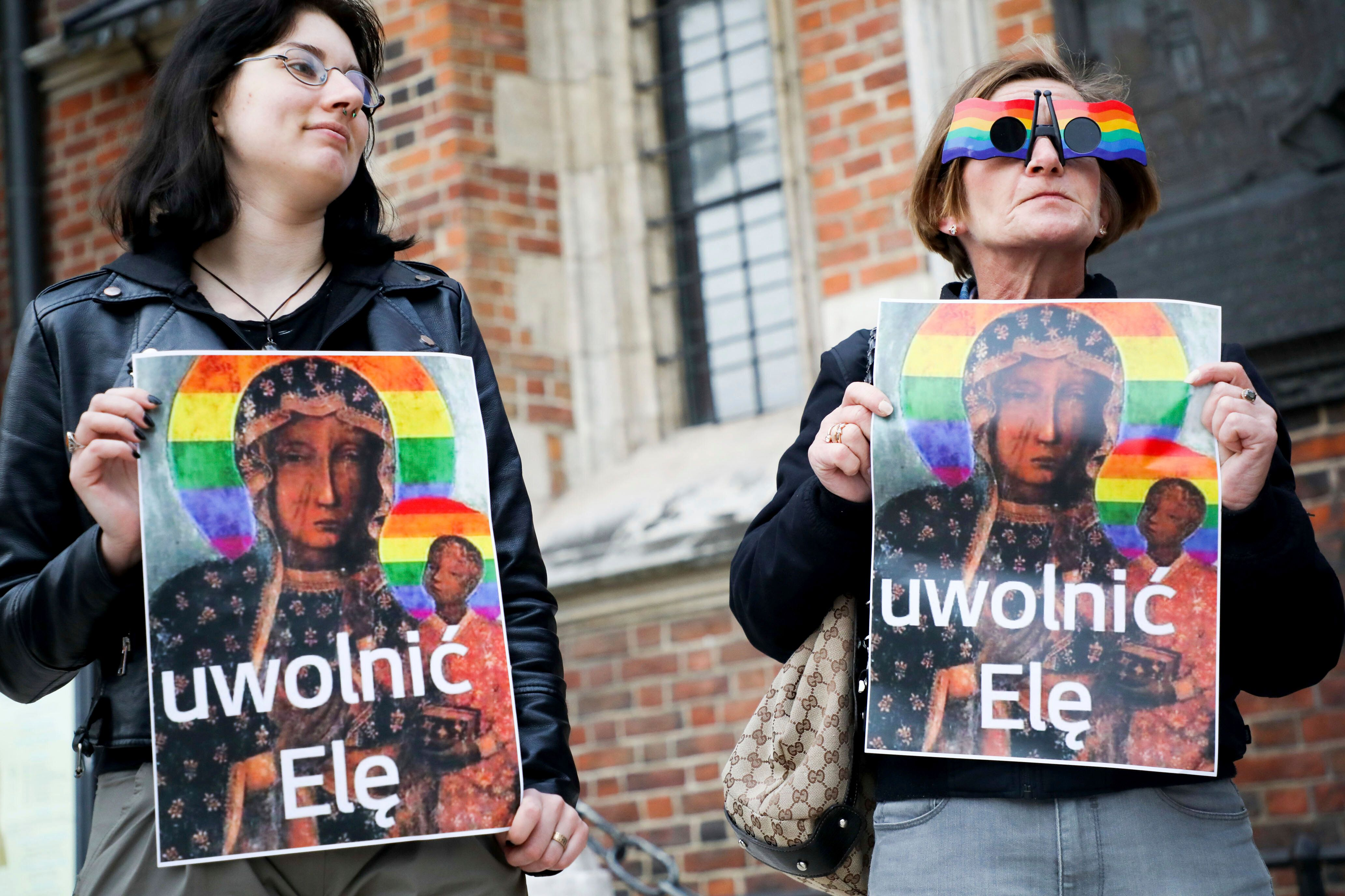 """Protesters in Krakow pose with an alternative version of a painting known as the """"Black Madonna of Częstochowa"""" o"""
