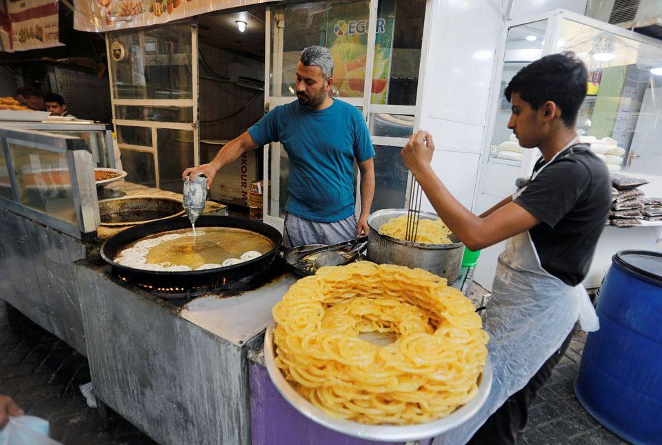 Irak - Des hommes préparent de la zlabiya, un dessert, à