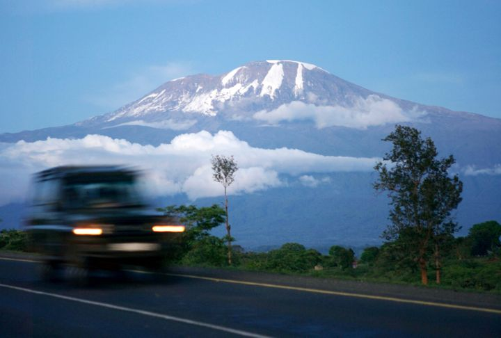 A vehicle drives past Mount Kilimanjaro in Tanzania's Hie district December 10, 2009. At the foot of Africa's snow-capped Mount Kilimanjaro, images of the mountain adorn the sides of rusting zinc shacks and beer bottle labels, but the fate of the real version hangs in the balance. REUTERS/Katrina Manson (TANZANIA ENVIRONMENT SOCIETY)