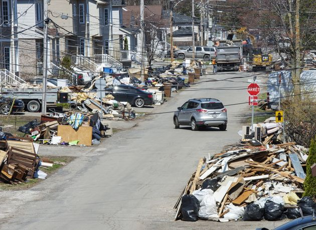 Les débris s'allignent sur le bord de la rue à Sainte-Marthe-sur-le-Lac alors que les résidents...
