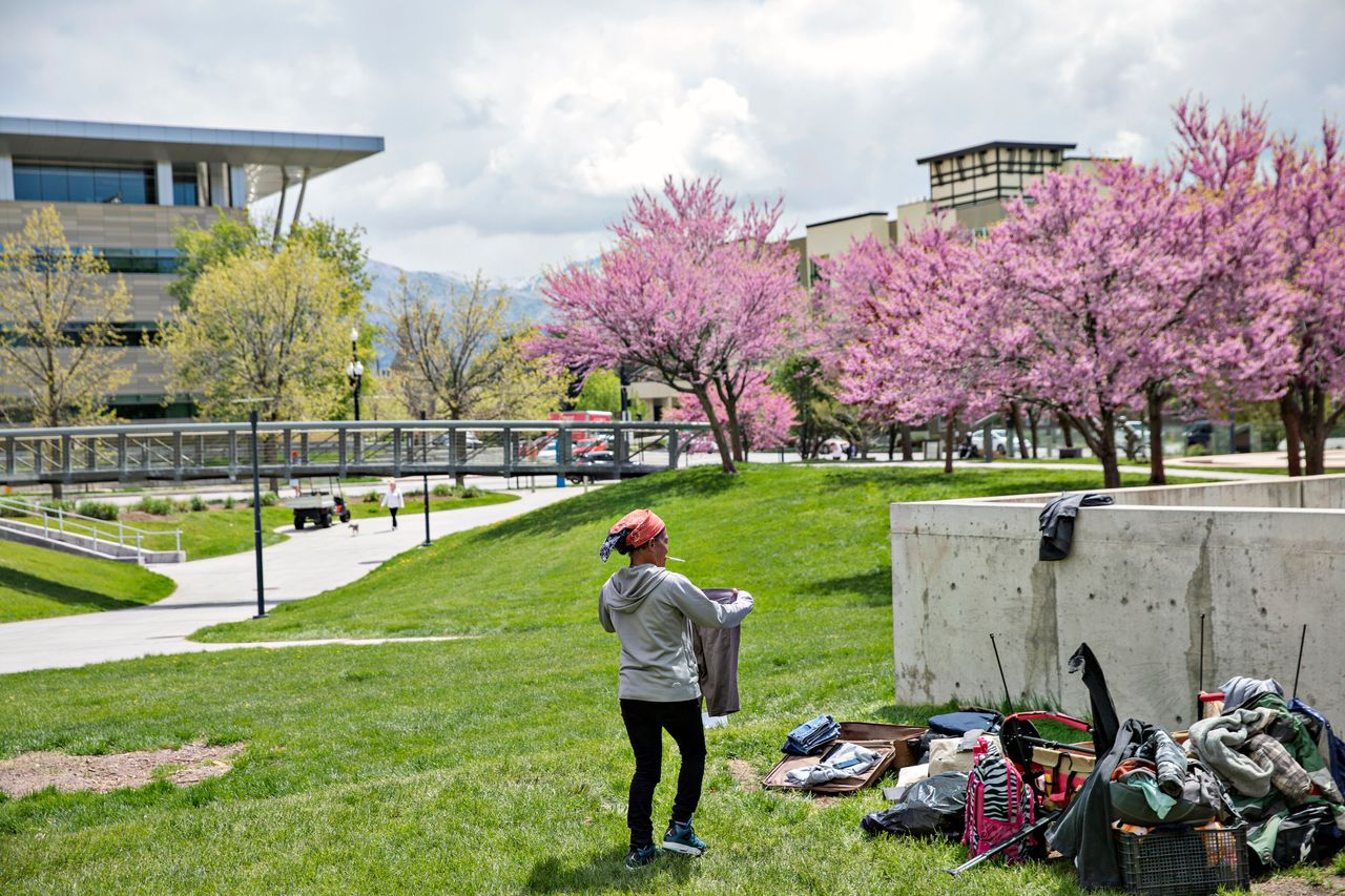 Dorriane Olson, 47, organizes her belongings in the courtyard at Library Square on May 1, 2019, in downtown Salt Lake City. Olson works a job overnight and tries to sleep during the day. She says she's been on a waiting list for housing for two years.