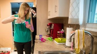 In this Aug. 1, 2018 photo, Lauren Woehr pours bottled water into her 16-month-old daughter Caroline's cup at their home in Horsham, Pa. In Horsham and surrounding towns in eastern Pennsylvania, and at other sites around the United States, the foams once used routinely in firefighting training at military bases contained per-and polyfluoroalkyl substances, or PFAS. EPA testing between 2013 and 2015 found significant amounts of PFAS in public water supplies in 33 U.S. states. (AP Photo/Matt Rourke)
