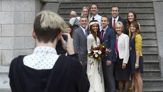 SALT LAKE CITY, UT - SEPTEMBER 27, 2014: An interracial couple pose for a photograph with members of their wedding party after their Mormon wedding ceremony in the Salt Lake Temple in Salt Lake City, Utah. Once condemned by The Church of Jesus Christ of Latter-day Saints, interracial marriages are now allowed by the Mormon church but are discouraged. (Photo by Robert Alexander/Getty Images)