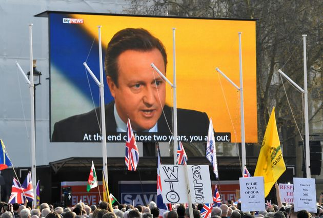 An outdoor screen displays a broadcast of former British Prime Minister David Cameron at the March to...