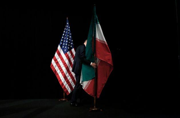 이란 핵협정(JCPoA·포괄적 공동행동계획)에 참여한 유엔 안전보장이사회 상임이사국 5개국(미국, 영국, 프랑스, 러시아, 중국)+독일(5+1)과 이란의 외교 대표자들이 협정 타결 기념촬영을 마친 뒤 한 관계자가 깃발을 옮기는 모습. 오스트리아, 빈. 2015년 7월14일.