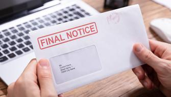 Close-up Of Person's Hand Holding Final Notice Envelope